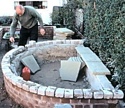 The pond is being built. A man is cementing the top of the pond wall. The base and sides of the pond are covered in concrete.